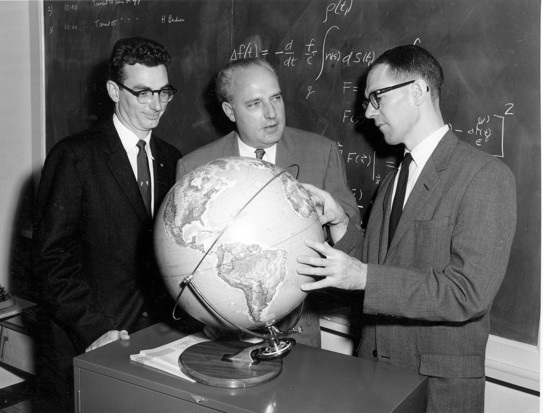 "Mathematician Bill Guier (l) and physicist George Weiffenbach (r), told APL Research Center director Frank T. McClure (c), about their success using Doppler tracking for satellites. ""McClure's brain started going into fast forward,"" remembered John Dassoulas. ""Knowing the navigational challenges the U.S. Navy faced, McClure said, 'Well, if you can find out where the satellite is, you ought to be able to turn that problem upside down and find out where you are.' """