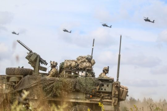 "An Interim Armored Vehicle ""Stryker"" and AH-64 Apache helicopters with Battle Group Poland move to secure an area during a lethality demonstration as part of Saber Strike 18 in June 2018. (Photo: U.S. Army/Spc. Hubert D. Delany III, 22nd Mobile Public Affairs Detachment)"