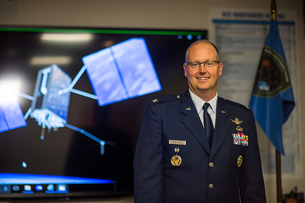Col. Whitney next to an artist's depiction of a GPS III satellite in orbit. (Photo: U.S. Air Force/Van Ha)