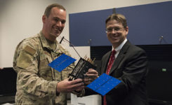 Johnathon Caldwell, Lockheed Martin Space vice president of navigation systems, right, presents Lt. Col. Stephen Toth, 2nd Space Operations Squadron commander, with a GPS III model satellite as a token of appreciation for the 2nd SOPS critical mission in space at Schriever Air Force Base, Colorado, July 29, 2019. The squadron performed its first station keeping maneuver on a GPS III satellite May 14, 2020, at Schriever AFB. (Photo: U.S. Air Force/1st Class Jonathan Whitely)