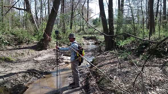 In Cleveland County, North Carolina, surveyor Adam Plumley determines exactly where a creek crosses a property line. (Photo: AP Surveying PLLC)