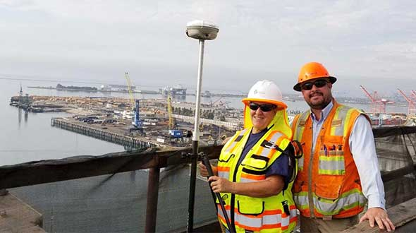 In Long Beach, California, correction services support the 250-foot-high Gerald Desmond Bridge project. Trevor Rice (left), president of D. Woolley & Associates, joins Kimberley Holtz, director of survey, Port of Long Beach. (Photo: Trimble)