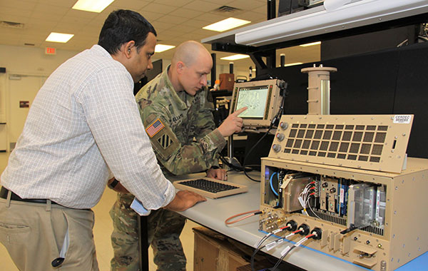 Andradige Silva, electronics engineer for the C5ISR Center's Intelligence and Information Warfare Directorate, and Maj. Doug Williams, assistant product manager for the Joint Battle Command-Platform, access the C4ISR/Electronic Warfare Modular Open Suite of Standards (CMOSS). (Photo: U.S. Army)