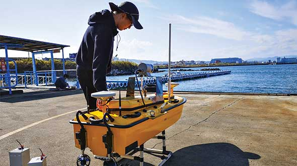 Weichao Liu, a member of CHC Navigation's technical support staff, prepares to launch an Apache6 unmanned surface vessel (USV), also known as a marine drone. (Photo: CHC Navigation)