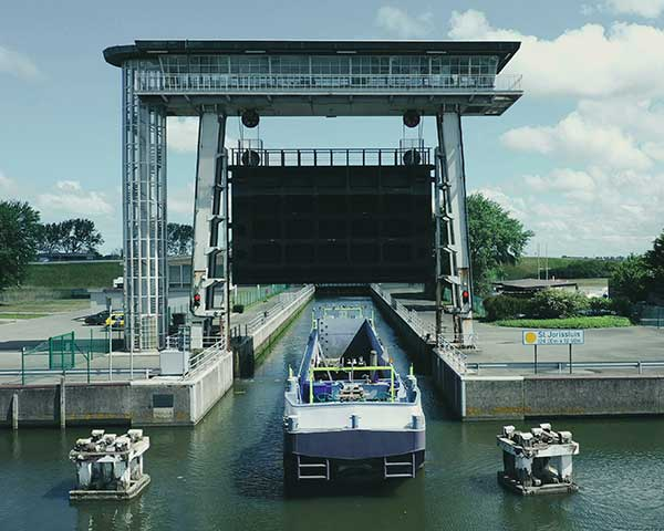 An autonomous freight barge moves through a lock. The barge is equipped with Septentrio GNSS positioning via Seafar navigation. (Photo: Seafar)
