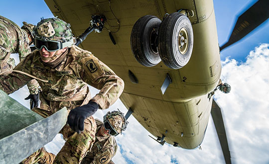 From his side window, a crew chief relays vital position information back to the CH-47 Chinook pilot as paratroopers hook their pallet of equipment to the underside of the helicopter during sling load and air operations training. (Photo: U.S. Army/Maj. Robert Fellingham)