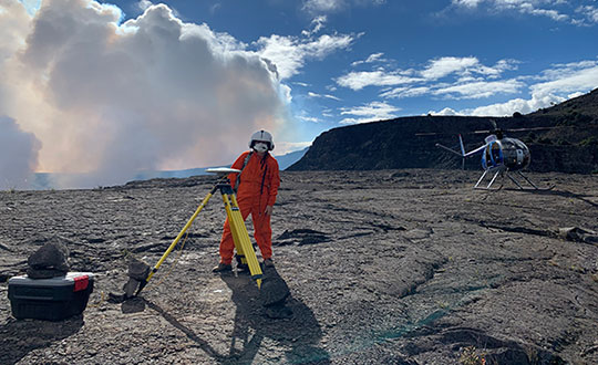 An HVO geophysicist deploys a GPS receiver on the Kilauea caldera floor to measure changes in ground motion. A volcanic gas plume rises in the background. (Photo: USGS)