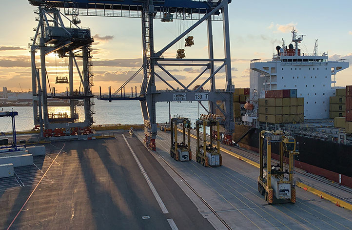 Locata-enabled manned straddles near STS cranes unload a ship at dusk. (Photo: Photo: David Small/Locata)