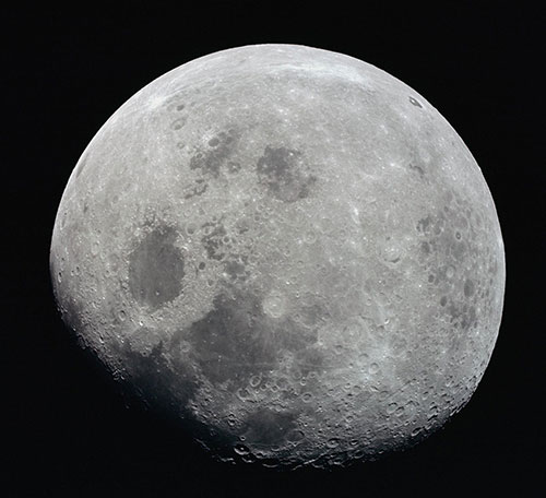 his photograph of a nearly full Moon was taken from the Apollo 8 spacecraft at a point above 70 degrees east longitude. Mare Crisium, the circular, dark-colored area near the center, is near the eastern edge of the Moon as viewed from Earth. (Credits: NASA)