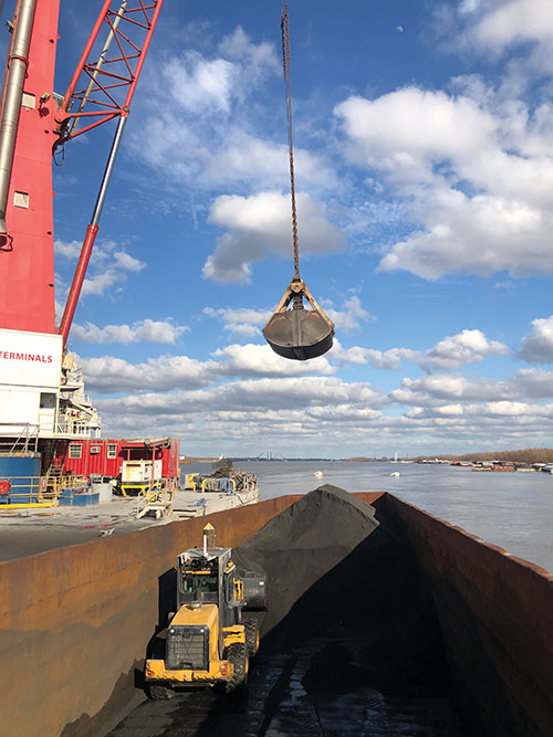 A remotely controlled front loader operates inside a barge. (Photo: Caterpillar)