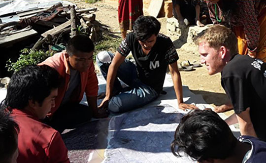 FIG Volunteer Community Surveyor working with locals to discuss parcel possession. (Photo: FIG Young Surveyors)