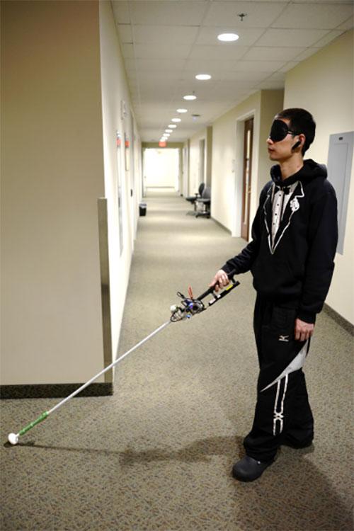 Study author Lingqiu Jin tests the robotic cane. (Photo: Cang Ye, VCU/NIH)