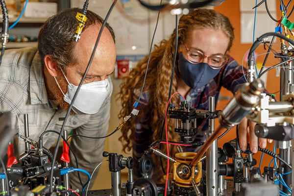 Sandia National Laboratories scientist Peter Schwindt, left, and postdoctoral scientist Bethany Little examine the vacuum package held in a yellow, 3D-printed mount. (Photo: Bret Latter/Sandia)