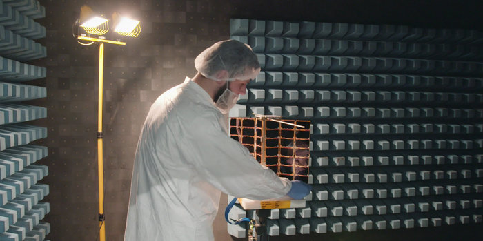 One of Spire's Satellite Manufacturing Technicians (Tomasz Chanusiak) tests the Radio Frequency capabilities of a LEMUR2 nanosatellite in Spire's cleanroom in Glasgow, Scotland. (Photo: ESA)