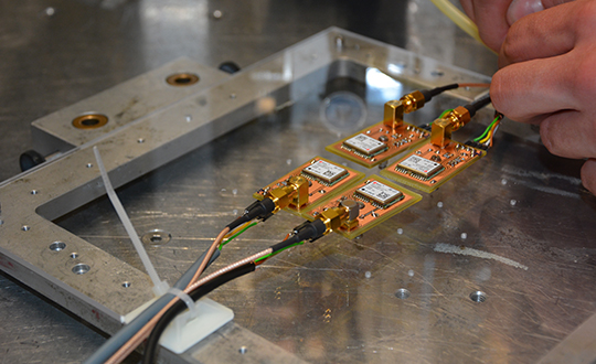 The Astrocast CubeSat's four u-blox receiver modules mounted on an acrylic glass to be placed into a proton radiation beam at the Paul Scherrer Institute in Switzerland. (Photo: ESA)